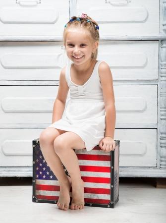 jolie petite fille: petite fille avec une valise dans les couleurs du drapeau américain