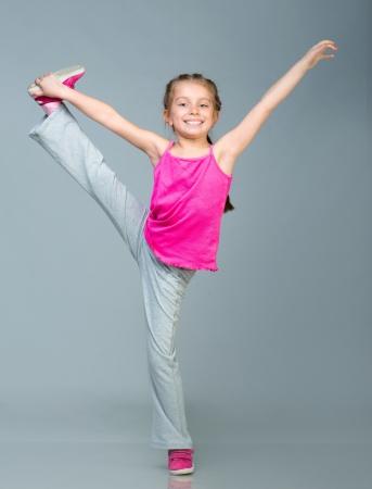 Little girl doing gymnastics exercise in studio