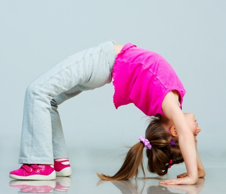 one little girl: Little girl doing gymnastics exercise