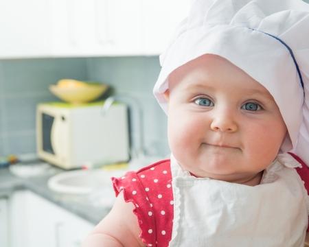 niñez: lindo bebé con el sombrero de un cocinero s en la cocina