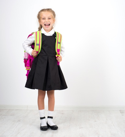 little cute girl with backpack on a white background photo