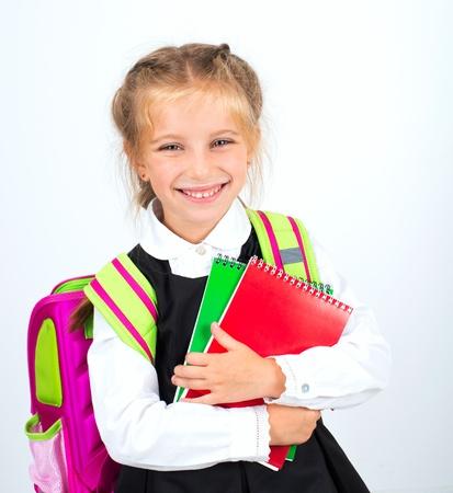 školačka: malá roztomilá usmívající se dívka s papírnictví na bílém pozadí