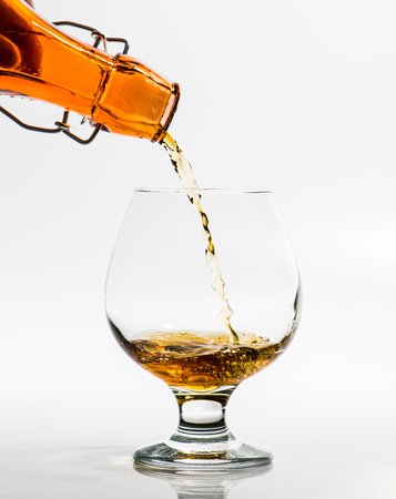 Pouring a glass of brandy from a bottle photo