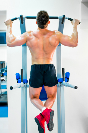 bodybuilder doing exercises on the horizontal bar photo