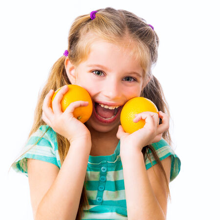 little smiling girl with two oranges isolated on white background photo