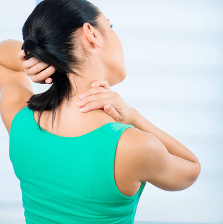 young brunette woman with a pain in the neck photo