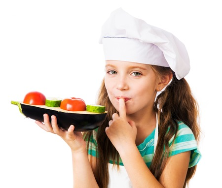 little girl in chef hat with sandwich from vegetables on a white background Фото со стока