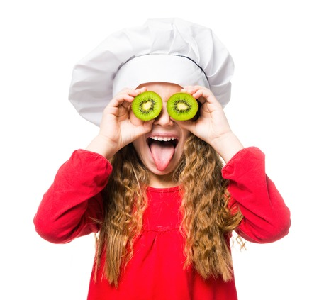 little girl in chef hat with dvemya rugs kiwi on eyes shows tongue