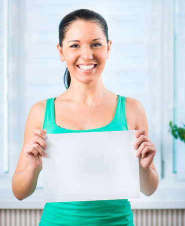 Portrait of happy young casual woman holding a blank signboard, horizontally photo