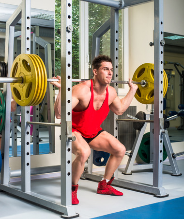 squats: weightlifter squats with a barbell