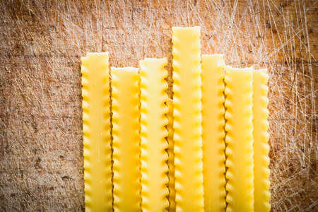 pasta isolated: uncooked pasta on a wooden cutting board