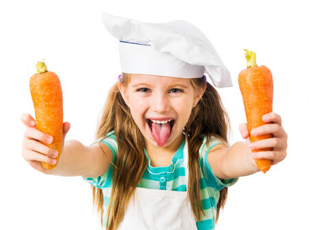 little girl in chef hat with two carrots shows tongue on a white background photo