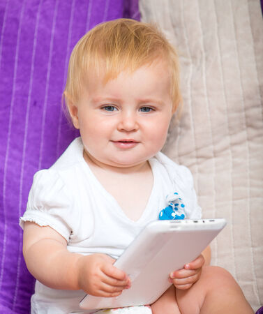 adorable baby with tablet PC photo