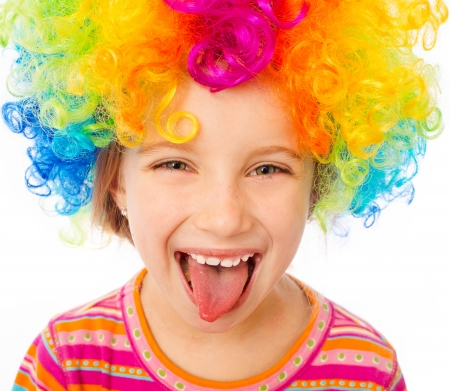 smiling little girl shows tongue in clown wig isolated on white background photo