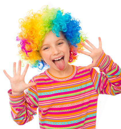 smiling little girl shows tongue and hands in clown wig isolated on white background Stock fotó