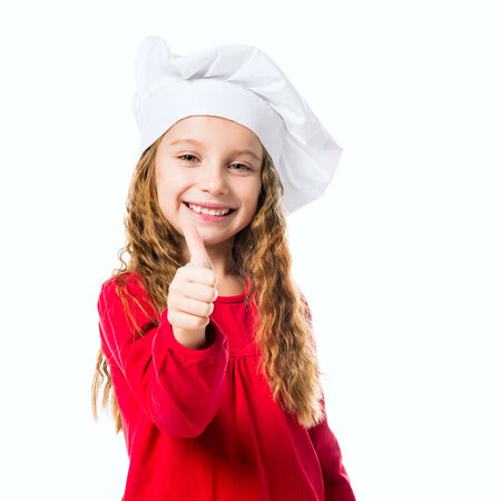 smiling little girl in chef hat with thumb up on white background photo