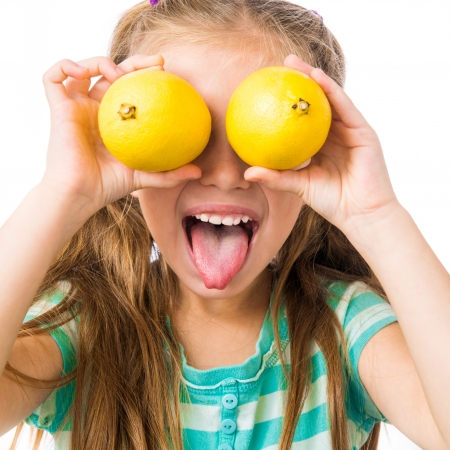 little girl with two lemons shows tongue isolated on white background photo
