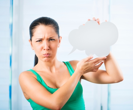 sulky: sulky young brunette woman holding a white cloud for text Stock Photo