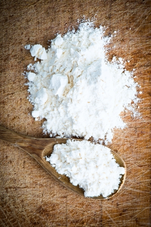 board: flour in a wooden spoon on a cutting board Stock Photo