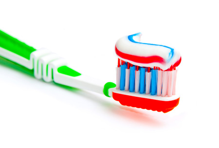 toothbrush with tricolor toothpaste isolated on a white  photo