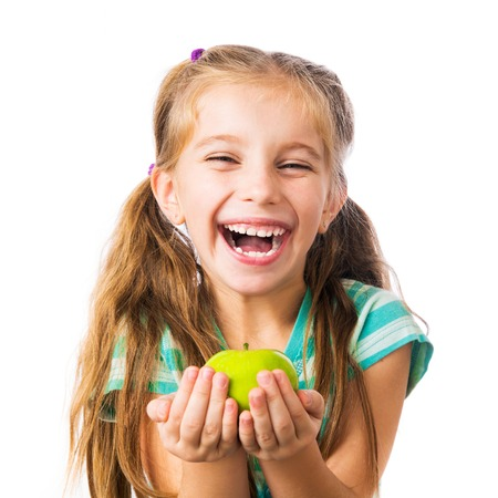 little girl laughing and holding an apple isolated on white background photo