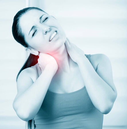 young brunette woman with a pain in the neck, monochrome photo with red as a symbol for the hardening photo