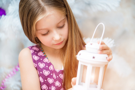 beautiful little girl holding a lantern