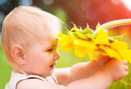 Cute baby with sunflower on summer field photo