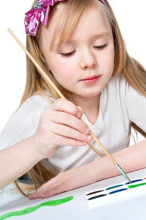 pretty little girl paints with a brush on paper photo