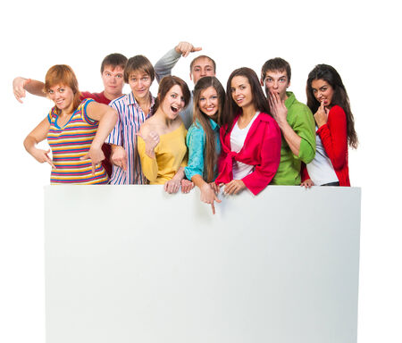 holding blank sign: Happy young group of people standing together and holding a blank sign for your text  isolated on white background
