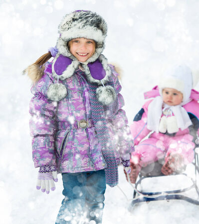 wintering: Smiling girl rolls brother on sledge on snow background