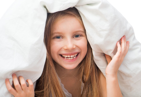 Laughing little girl under a blanket  Isolated on white