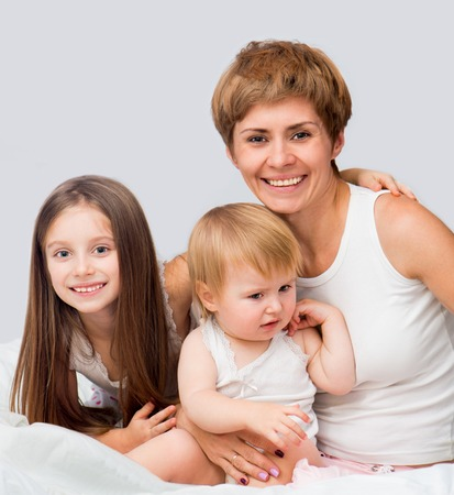 Happy mother with her ​​son and daughter sitting on a bed  photo