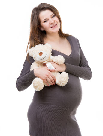 beautiful young pregnant woman in a gray dress with a teddy bear isolated on white background photo