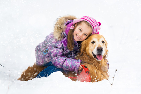 smiling little girl hugging dog in snow photo