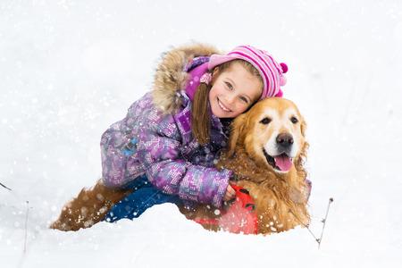 smiling little girl hugging dog in snow