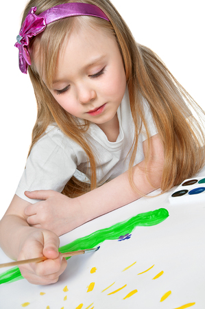 pretty little girl paints a watercolor painting photo