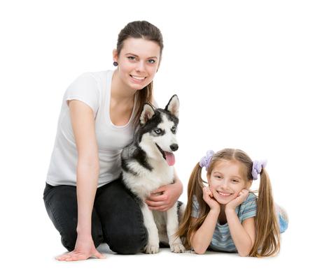 mujer con perro: dos hermanas sonrientes y un perro husky sentado en el suelo sobre un fondo blanco