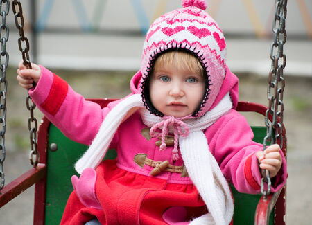 playground ride: Cute Little girl on the playground ride on a swing