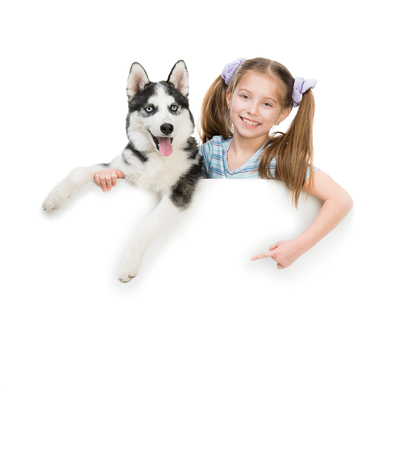 happy little girl and dog Husky with white cardboard photo
