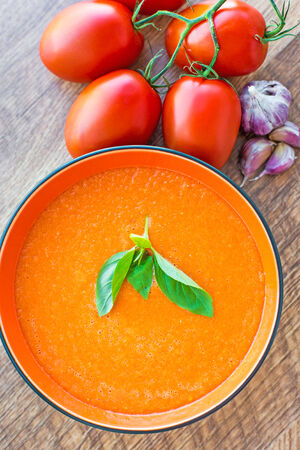 gaspacho: A bowl of tomato soup gaspacho with basil, tomatoes and garlic