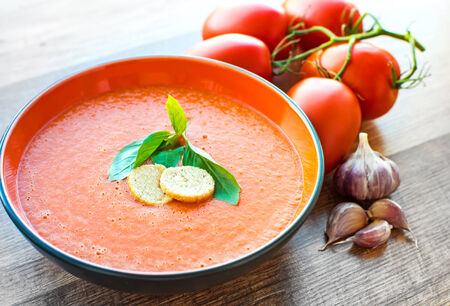 cold soup: A bowl of tomato soup gaspacho with basil and crackers Stock Photo