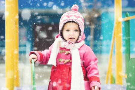 white  hat: Baby girl playing on winter playground Stock Photo
