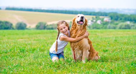 Little girl sitting on the grass with labrador retriever in the summer park. Looking into the camera.