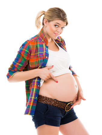 expectant arms: Beautiful pregnant white woman wearing shirt with hands on belly isolated on a white background