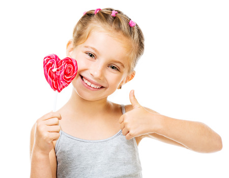 Adorable little girl with red lollipop in heart shape isolated over white background photo