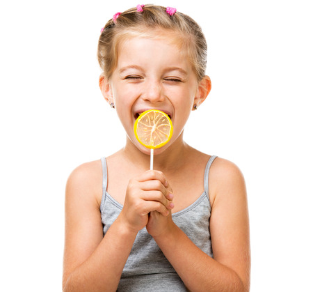 Adorable little girl with yellow lemon lollipop isolated over white background photo