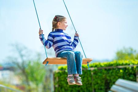 girl on swing: happy little girl on swing