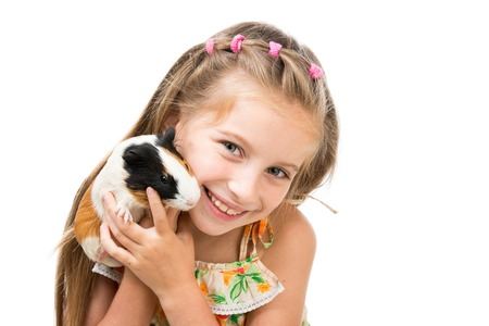 Cute little girl holding a guinea pig. Isolated on white background. photo