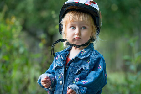 Cute little girl with sport helmet for bicycle, roller or skate photo